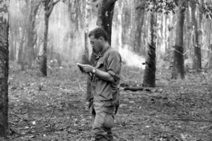 US soldier in Vietnam rubber plantation reads mail