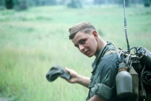 young US soldier carries radio on Vietnam patrol