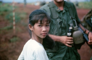 Vietnamese girl sells coca cola to American soldier